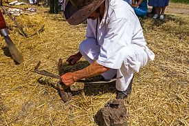 foto of scythe  - Man with hammer and iron tool on the tree stump is sharpening his scythe - JPG