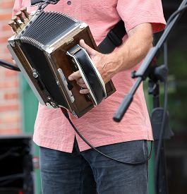 pic of accordion  - Zydeco accordion musician performing at a cajun music festival outdoors - JPG