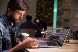 stock photo of late 20s  - Office Worker With Coffee At Desk Working Late On Laptop - JPG