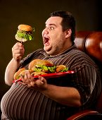 Diet failure of fat man eating fast food hamberger. Happy smile overweight person who spoiled health poster