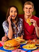 Couple eating fast food. Man and woman eat hamburger with ham. Friends holding two burder junk on da poster