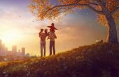 Happy family at sunset. Father, mother and two children daughters having fun and playing on autumn n poster