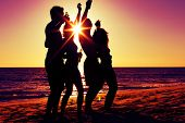 People (two couples) on the beach having party, drinking and having a lot of fun in the sunset (only