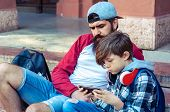 Trendy Boy Teenage With Bearded Dad Playing A Game On The Phone. Family Relationship Father And Teen poster