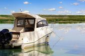 Big Luxury Fishing Boat With Cabin Moored Near River Or Lake Shore In Still Water. Blue Sky On The B poster