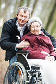 Caregiver careful man walking and embracing disabled senior woman grandmother at wheelchair in natur