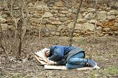 Poor Homeless Man Lying On Ground In City Park poster