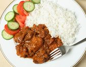 A plate of chicken tikka masala with basmati rice and a salad of cucumber and tomato.