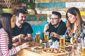 Young People Enjoying Time Together Eating Burgers And Pizza At Restaurant - Happy Group Of Friends  poster