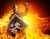 stock photo of crusader  - Medieval knight in attack position on fire background - JPG