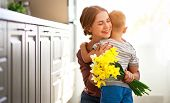 Happy Mothers Day! Child Son Gives Flowersfor  Mother On Holiday . poster