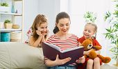 happy loving family. pretty young mother reading a book to her daughters poster