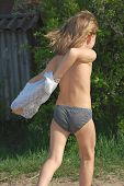 stock photo of wet pants  - Happy little girl is taking off her wet clothes after swimming in the river - JPG