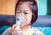 Sad Asian Child Holds A Mask Vapor Inhaler For Treatment Of Asthma. Breathing Through A Steam Nebuli poster