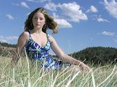 stock photo of titillation  - Teen with hair flying sitting in the grass - JPG