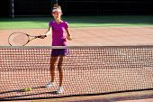 Young Woman In Cap And Tennis Uniform Serving Tennis Ball During Training On The Outdoor Tennis Cour poster