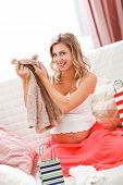 Smiling Pregnant Examines Purchases For Baby
