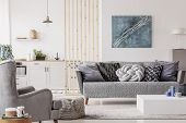 Open Plan Studio Apartment With Small White Kitchen And Living Room With Grey Couch And Wooden Coffe poster