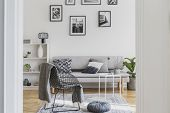 Fancy Black Metal Chair With Grey Blanket Next To Grey Pouf In Trendy Living Room poster