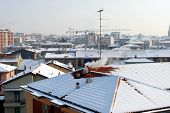 snow covered rooftops with smoking chimneypots