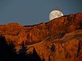 Moonrise behind mountain