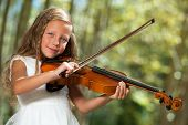Cute Girl In White Playing Violin Outdoors.