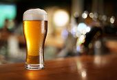 stock photo of pitcher  - Glass of light beer on a dark pub - JPG