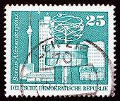 Постер, плакат: Почтовая марка ГДР 1973 года мировые часы Александр площадь Берлин
