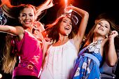image of party people  - Three smart dancers moving at disco while raising their arms - JPG