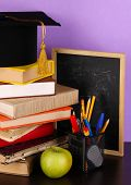 Books and magister cap against school board on wooden table on purple background