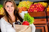 stock photo of local shop  - Happy woman at the local market buying groceries - JPG
