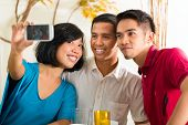 Asian friends, two men and a woman, having fun taking pictures with mobile phone