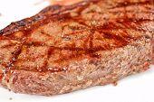 Juicy rib-eye beef steak on a white plate