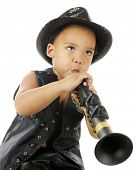 A biracial preschooler playing a clarinet in a sparkly black fedora and black leather vest.  On a wh