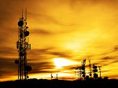 Several radio towers with sunset sky in background
