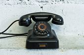 stock photo of rotary dial telephone  - Old black telephone with rotary dial in white room - JPG