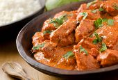 stock photo of ghee  - A bowl of creamy butter chicken curry with basmati rice and limes - JPG