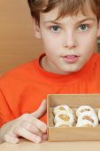 Boy in orange t-shirt holds open box of corrugated cardboard with cookies with almonds and icing sugar