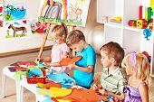 stock photo of preschool  - Child boy cutting out scissors paper in preschool - JPG