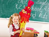 Child holding school cone standing near blackboard.