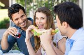 Happy Group Of Friends Eating Sandwich With Fun Outdoor