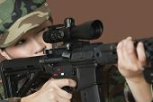 stock photo of corps  - Young female US Marine Corps soldier aiming M4 assault rifle over brown background - JPG