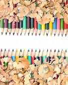 Colorful pencil with colorful pencil shavings on white background