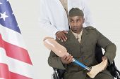 Doctor with disabled military officer holding artificial limb as he looks at American flag
