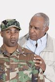 picture of military personnel  - Portrait of an African American US Marine Corps soldier with father over gray background - JPG