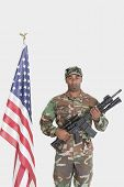stock photo of m4  - Portrait of US Marine Corps soldier with M4 assault rifle standing by American flag over gray background - JPG