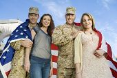 Low angle portrait of happy military couples wrapped in American flag against sky