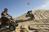 Side view of young men riding quad bikes over sand dunes in desert