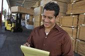Happy middle aged man writing on notepad with worker working in forklift at warehouse