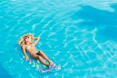stock photo of suntanning  - Young blonde woman with straw hat relaxing at the swimming pool - JPG